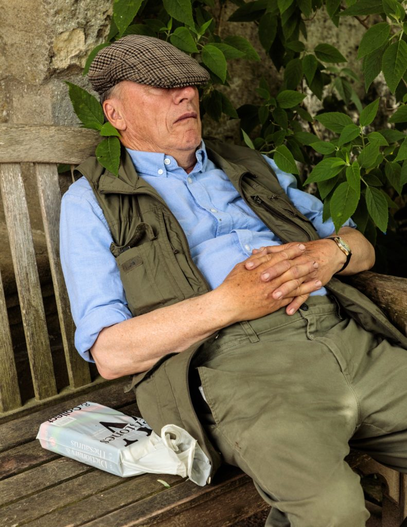 A man snoozing on a bench at the Oxford Botanic Garden & Arboretum